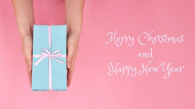 Une femme tenant en mains boîte-cadeau de noël ou du nouvel an