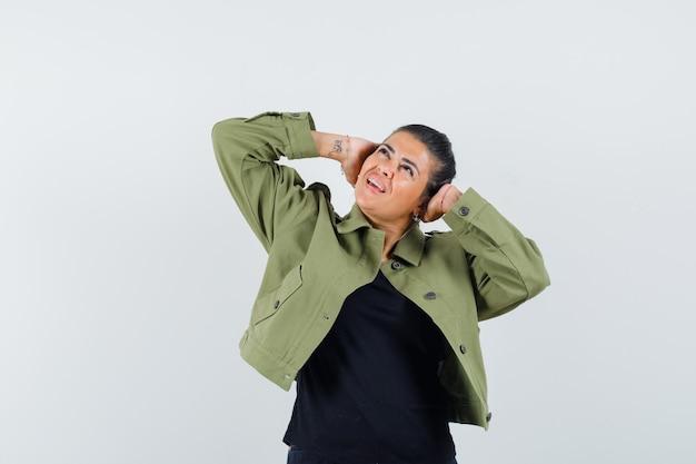Femme tenant les mains sur les oreilles en veste, t-shirt et à la peur