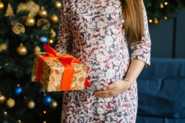 Femme tenant les mains sur son ventre de femme enceinte, les lumières de noël du sapin et tenant un cadeau