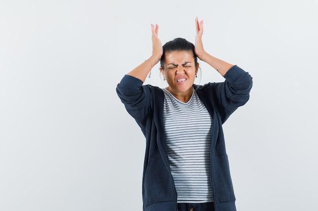 Femme tenant les mains sur la tête en t-shirt