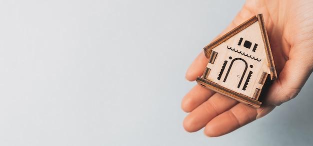 Femme tenant une maison en bois avec ses mains avec le soleil sur un fond bleu clair. douce maison