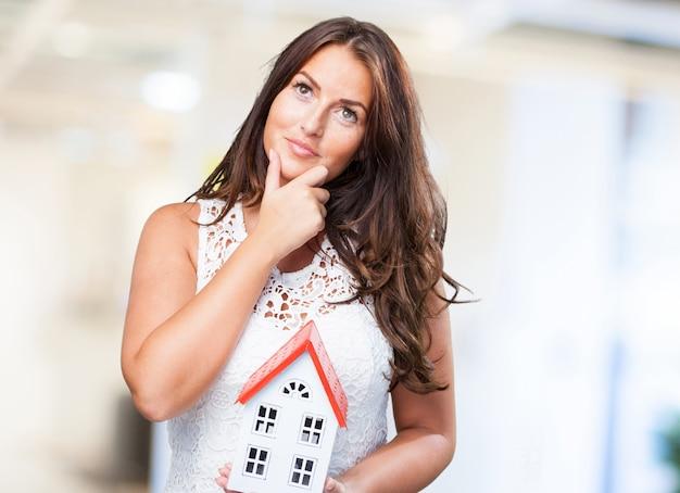 Femme tenant une maison et penser à quelque chose