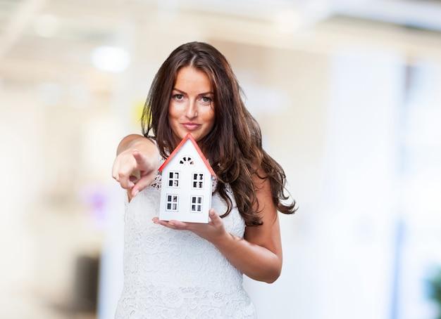 Femme tenant une maison et pointant vers l'avant