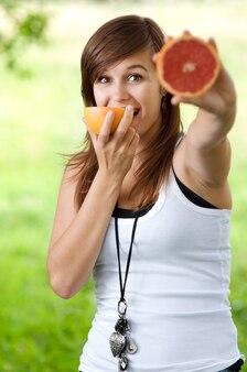 Femme tenant et mangeant du pamplemousse
