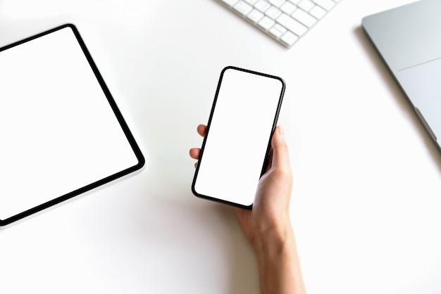 Femme tenant la maquette d'un smartphone d'écran blanc sur la table et l'ordinateur portable.