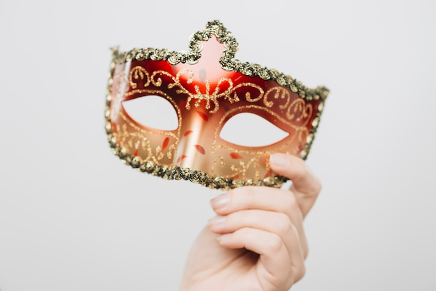 Femme tenant un masque de carnaval rouge à la main