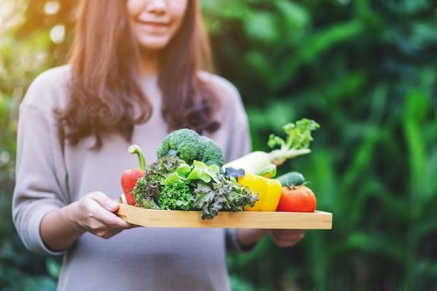 Une femme tenant un mélange de légumes frais dans un plateau en bois