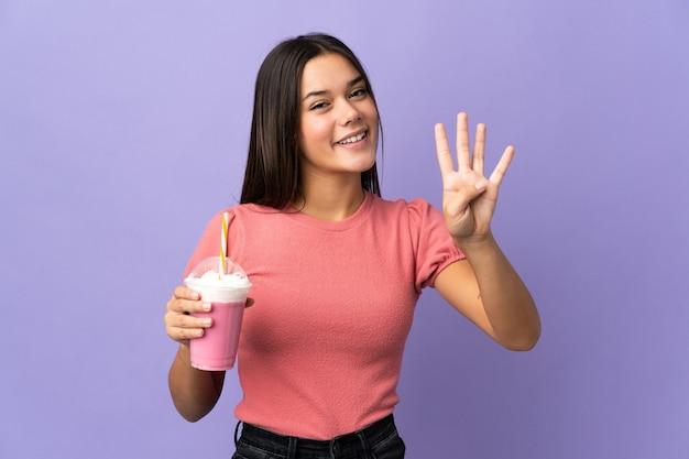 Femme tenant un milk-shake aux fraises heureux et en comptant quatre avec les doigts