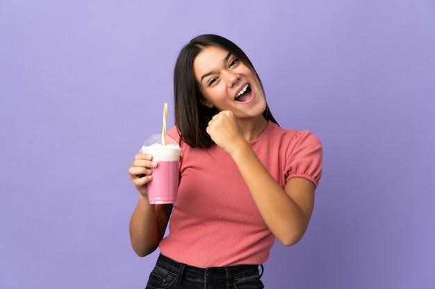Femme tenant un milkshake aux fraises célébrant une victoire