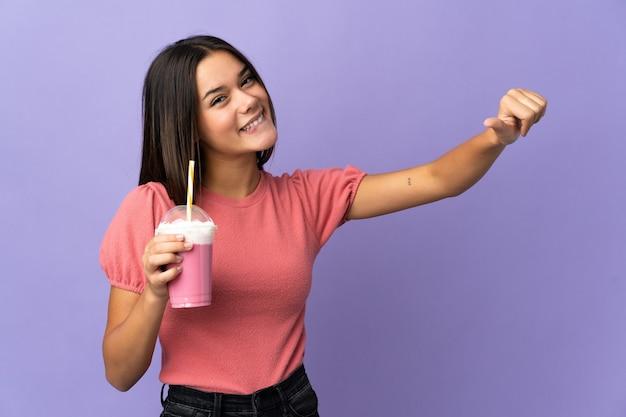 Femme tenant un milkshake aux fraises donnant un geste de pouce en l'air
