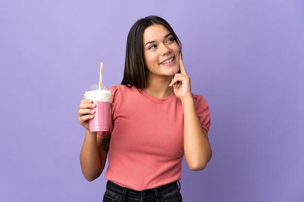 Femme tenant un milkshake aux fraises en pensant à une idée tout en levant