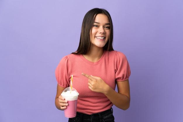 Femme tenant un milkshake aux fraises pointant vers le côté pour présenter un produit