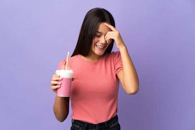 Femme tenant un milkshake aux fraises en riant