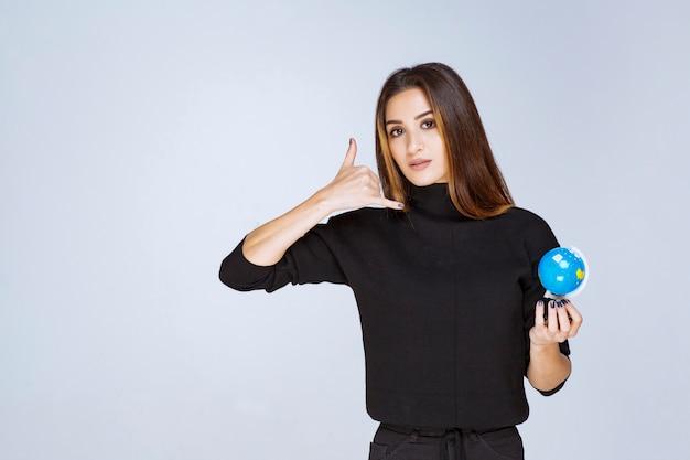 Femme tenant un mini globe et demandant un appel.