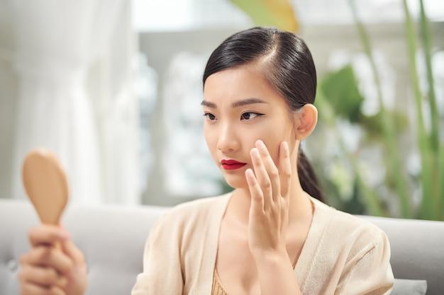 Femme tenant un miroir, toucher et s'inquiéter de son visage
