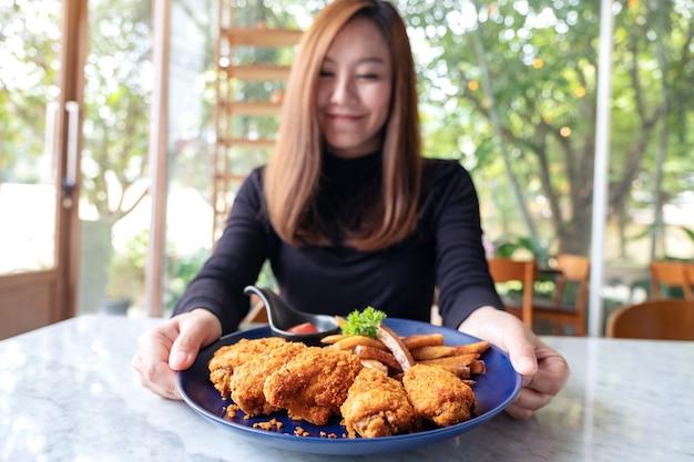 Une femme tenant et montrant une assiette de poulet frit et frites au restaurant