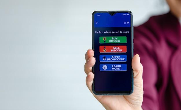 Femme tenant et montrant des écrans de smartphones avec des boutons pour acheter et vendre dans une application pour le commerce d'argent numérique bitcoin ou crypto-monnaie avec espace de copie.