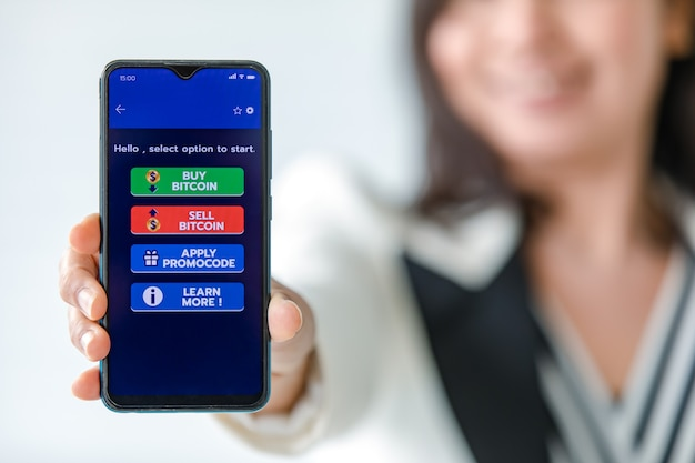 Femme tenant et montrant des écrans de smartphones avec des boutons pour acheter et vendre dans une application pour le commerce d'argent numérique en bitcoin ou en crypto-monnaie.