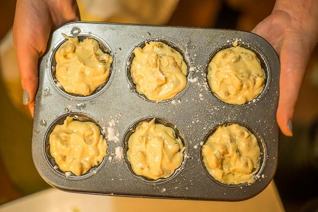Femme tenant des muffins crus sous forme de muffins