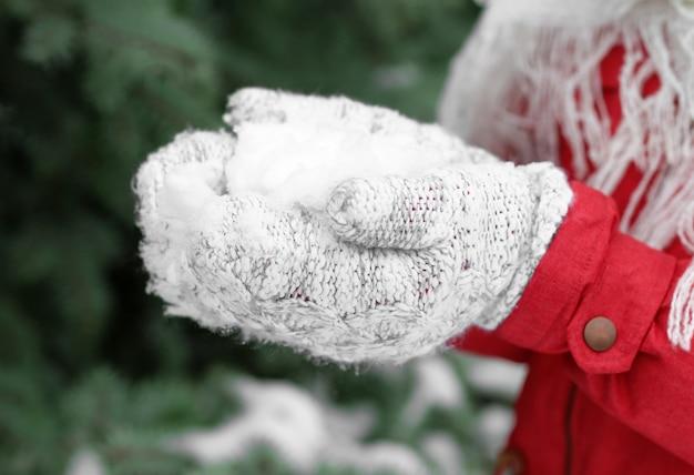 Femme tenant la neige dans les mains, gros plan