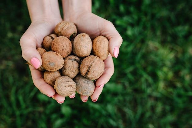 Femme tenant une noix entière dans ses mains