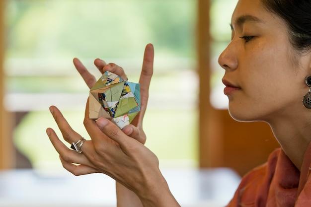 Femme tenant un objet en origami