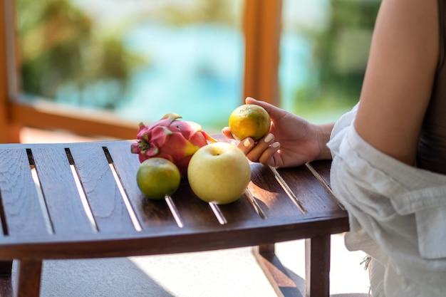 Une femme tenant une orange avec poire et fruit du dragon sur une petite table en bois