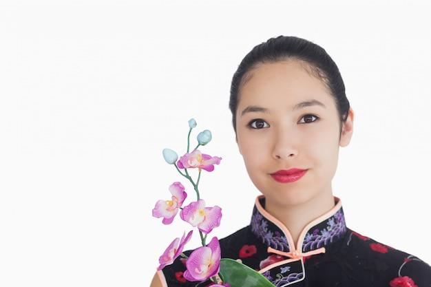 Femme tenant une orchidée en souriant
