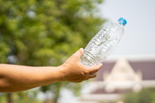 Une femme tenant des ordures de bouteilles en plastique se prépare à jeter à la poubelle.