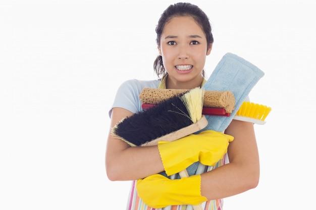 Femme tenant des outils de nettoyage lourds
