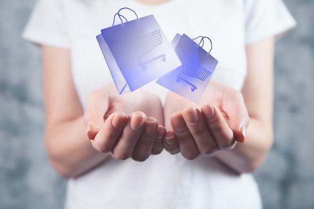 Femme tenant des packages virtuels pour achat en ligne. panier