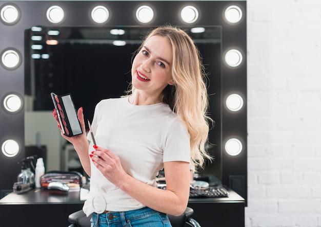 Femme tenant une palette de couleurs avec du rouge à lèvres et un pinceau