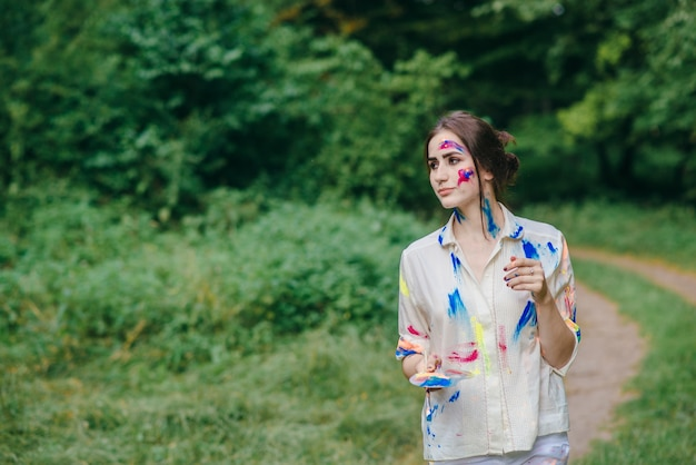 Femme tenant une palette de peinture tout en marchant