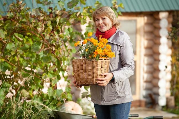Femme tenant un panier de fleurs jaunes dans le jardin