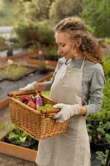 Femme tenant un panier de légumes coup moyen