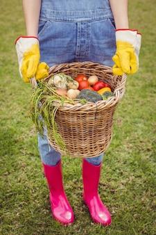 Femme tenant un panier de légumes fraîchement récoltés dans le jardin