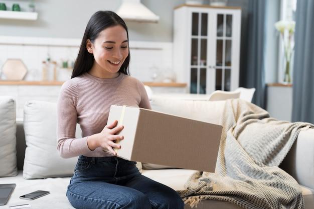 Femme tenant le paquet qu'elle a reçu après avoir acheté en ligne