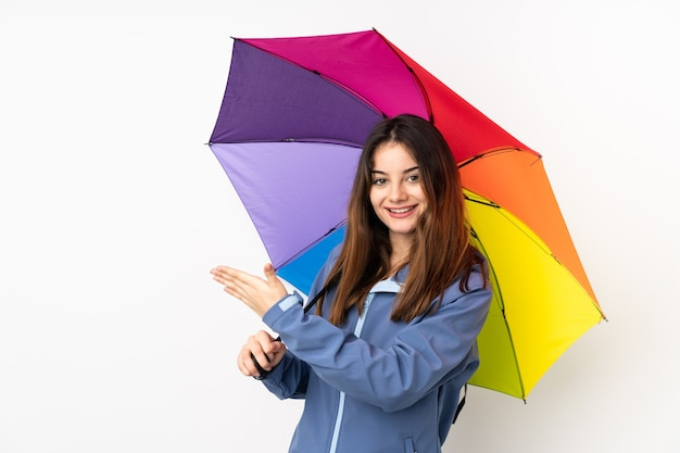 Femme tenant un parapluie isolé sur blanc étendant les mains sur le côté pour inviter à venir