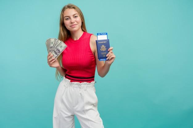 Femme tenant un passeport avec billets et argent