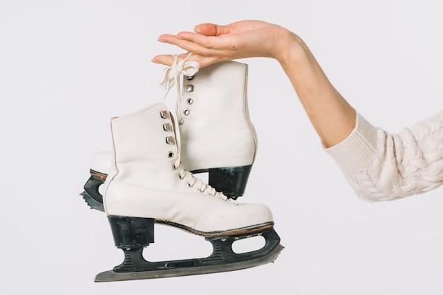 Femme tenant des patins blancs à la main