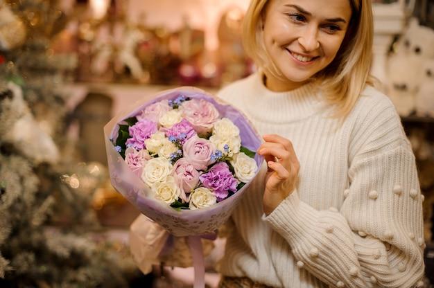 Femme tenant un petit bouquet de fleurs violettes et blanches enveloppées dans du papier cadeau