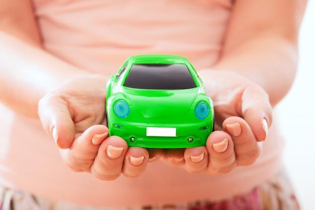 Femme tenant une petite voiture dans ses mains