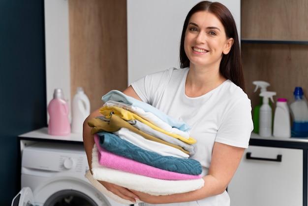 Femme tenant une pile de vêtements propres