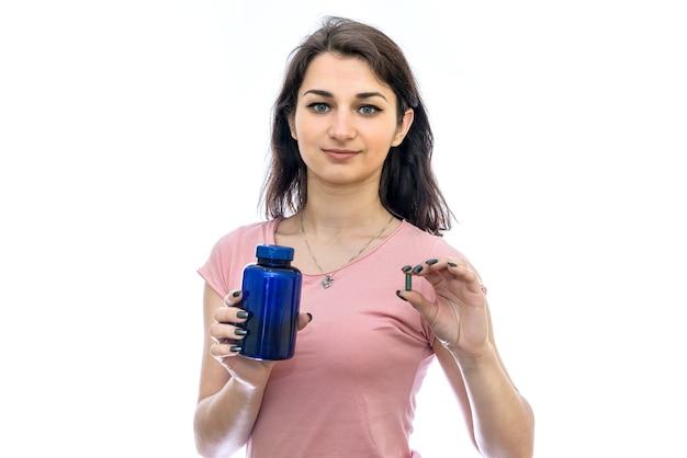 Femme tenant la pilule et la bouteille en verre isolé sur blanc