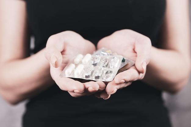 Femme tenant la pilule et le verre d'eau dans les mains en prenant des médicaments d'urgence