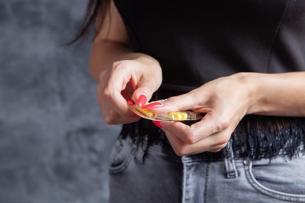 Femme tenant des pilules dans ses mains