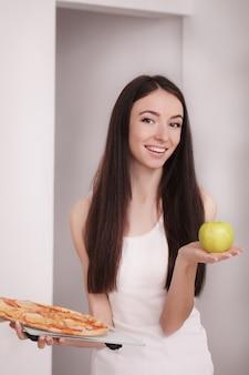 Femme tenant une pizza.