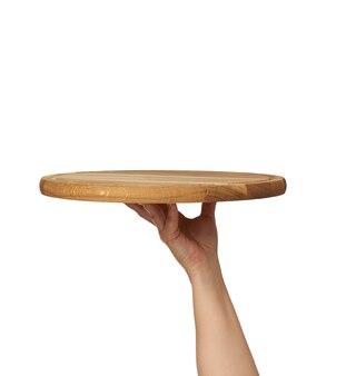 Femme tenant une planche à pizza en bois ronde vide