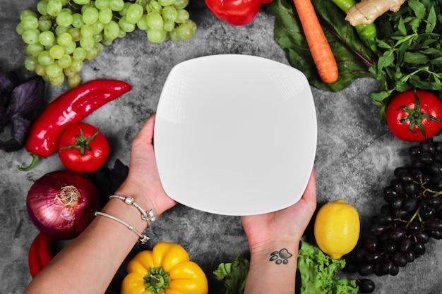 Femme tenant une plaque blanche sur fond de marbre avec des légumes frais.
