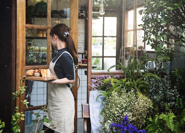 Femme tenant un plateau avec du pain dans un magasin de fleurs